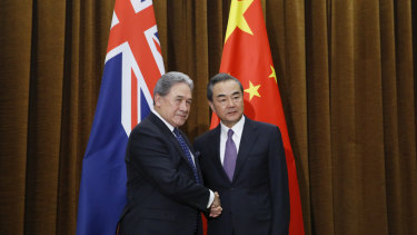 Which flag is that? NZ acting PM Winston Peters, left, shakes hands with Chinese Foreign Minister Wang Yi.