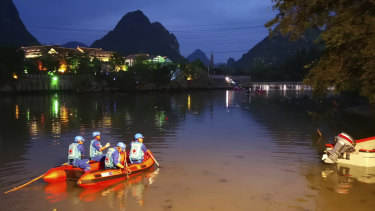 Rescuers search for missing boaters on the Taohua River in Guilin, in southern China.