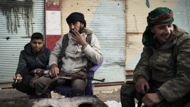 US-backed Syrian Democratic Forces  fighters sit outside a building as the fight against Islamic State militants continues in the village of Baghouz, Syria, on Saturday.