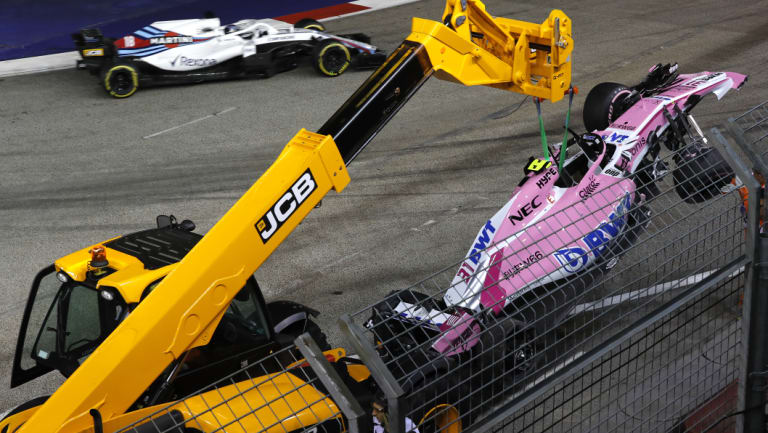 Bad books: A crane lifts Esteban Ocon's damaged Force India from the track after he crashed with teammate Sergio Perez.