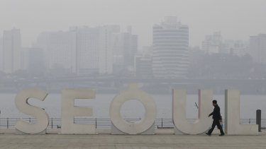 A man wearing a mask to protect himself from air pollution walks along the Han river at a park in Seoul, South Korea, on Tuesday.