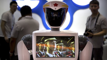 Chinese People's Liberation Army soldiers play in a video on the chest screen of a robot from Chinese robot maker Jiangsu Eastern Golden Jade Intelligent Robot Co.