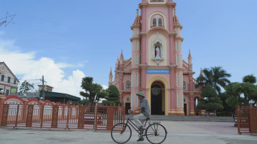 A man rides his bicycle past a Catholic church in the Dien Thinh village from where many of the victims came from.