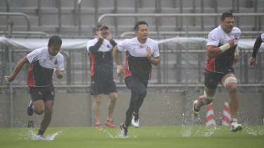 Rain or shine: Japan endure the big wet for theair captain's run.