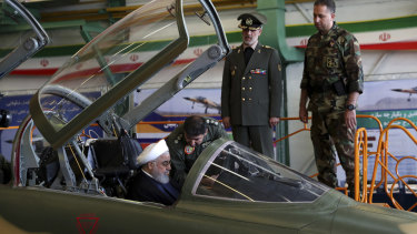 Iranian President Hassan Rouhani is briefed by an air force pilot as he sits in the cockpit of a fighter jet, before an inauguration ceremony of the aircraft in Iran on Tuesday.