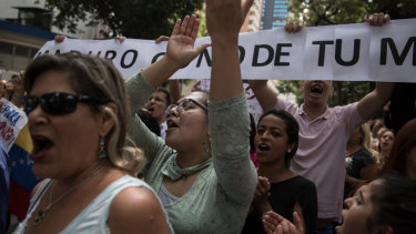 Demonstrators hold signs and shout slogans during a protest against Nicolas Maduro in Caracas on Wednesday.