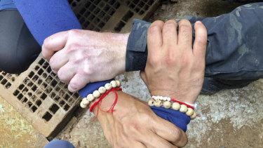 Three hands interlocked showing solidarity between Thai and international rescue workers.