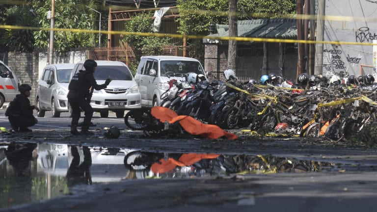 Members of a police bomb squad inspect the wreckage of motorcycles at the site where an explosion went off outside a church in Surabaya, East Java.