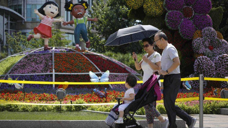 """A couple and a child walk by a decoration titled """"Common Prosperity"""" set up for the Forum on China-Africa Cooperation in Beijing."""