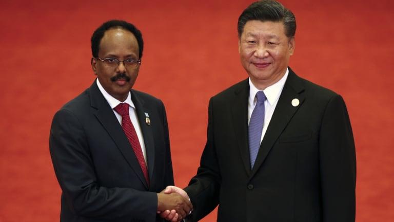 Somalia's President Mohamed Abdullahi Mohamed shakes hands with Xi Jinping.