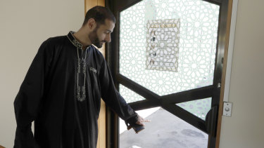 Khaled Alnobani gestures as he explains his escape through a glass door panel. He thinks as many as 17 people may have died trying to get out through the door.