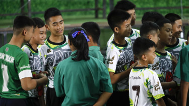Members of the rescued soccer team and their coach are greeted by their friends before the press conference.