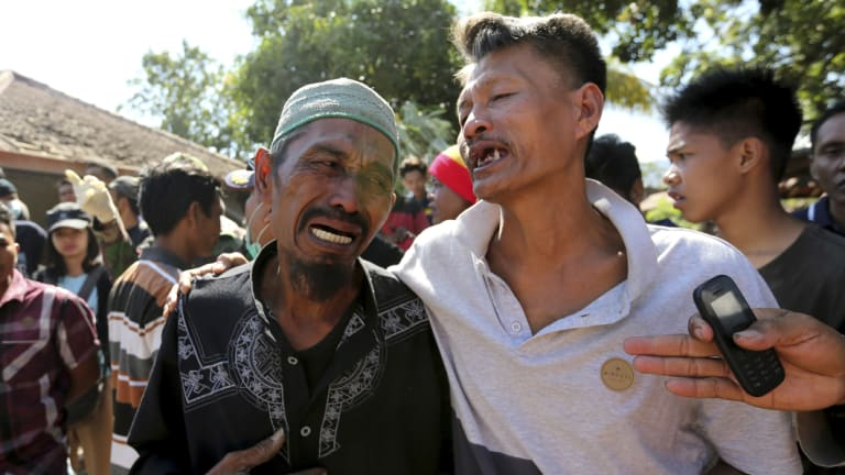 Relatives react as rescue teams recover the bodies of victims killed in an earthquake in North Lombok.