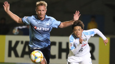 Sydney FC defender Ryan Grant (EFT) competes with Frontale's Tatusya Hasegawa.