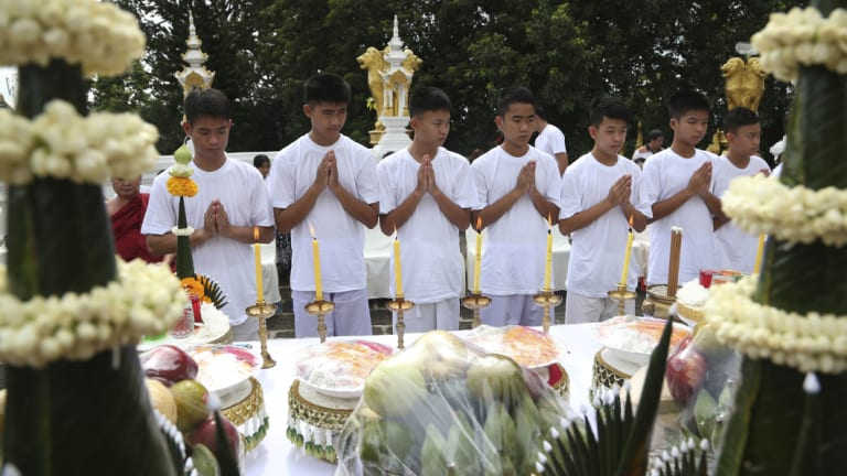 Eleven of the boys and their coach  attend the merit-making ceremony at a Buddhist temple.