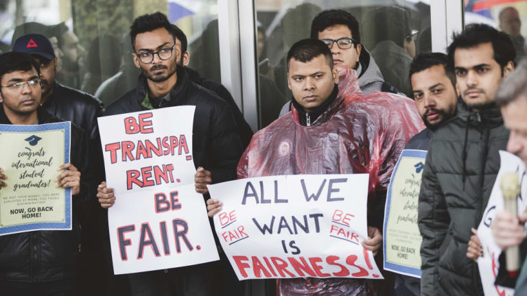 International students protest outside the Legislative Assembly against changes to the ACT government's visa program.