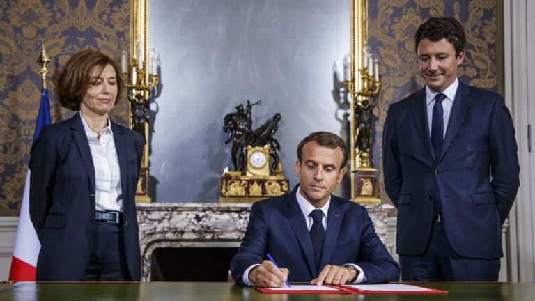 French President Emmanuel Macron, center, flanked by French Defence Minister Florence Parly, left, and French government spokesman Benjamin Griveaux, signs the armed forces annual law budget, at the Hotel de Brienne, in Paris in July.