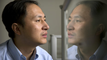 He Jiankui is reflected in a glass panel as he works at a computer at a laboratory in Shenzhen.