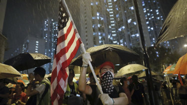 A protester waves a US flag as hundreds of protesters gather outside Kwai Chung police station in Hong Kong.