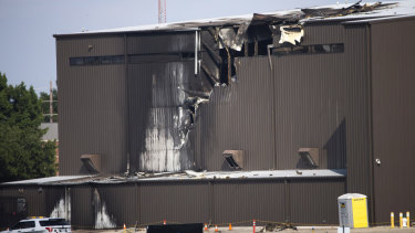 Damage is seen to a hangar after a twin-engine plane crashed into the building at Addison Airport in Addison, Texas.
