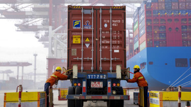 Workers check on a container before loading it to a cargo ship at the Qingdao port in east China's Shandong province.