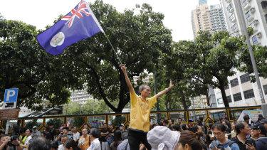 A protester waves a colonial British-era Hong Kong flag.