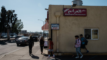 Children pass by Alazayem Restaurant in El Cajon.