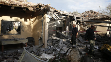 Police officers inspect the damage to a house hit by a rocket in Mishmeret, central Israel, on Monday.