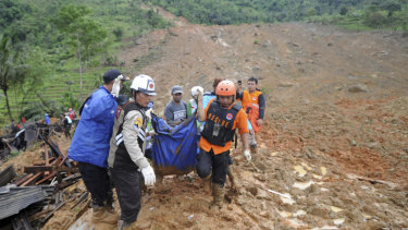 Rescuers carry the body of a landslide victim in Sirnaresmi, West Java.