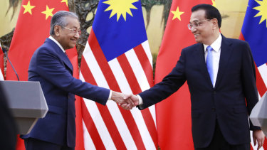 Malaysian Prime Minister Mahathir Mohamad shakes hands with his Chinese counterpart Li Keqiang in Beijing on Monday.