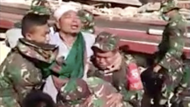 A man is carried by Indonesian military from a collapsed mosque in Lombok.