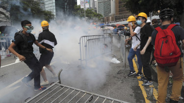 Protestors react to tear gas during a large protest near the Legislative Council in Hong Kong on Wednesday.