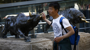 A man touches a bull statue outside a bank in Beijing. Chinese shares tumbled after President Donald Trump tweeted a threat to raise more tariffs on imports from China, spooking investors who had been expecting good news this week.
