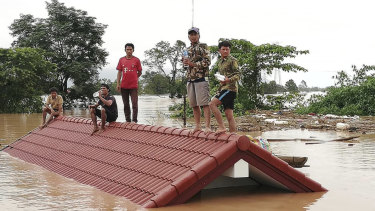 Villagers take refuge on a rooftop above flood waters from a collapsed dam in the Attapeu district of south-eastern Laos.