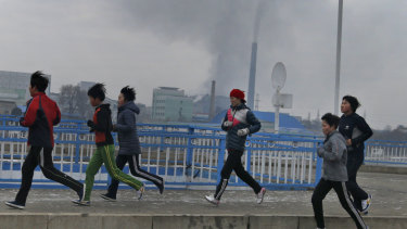 Young joggers pass by as smokes billows from the stack of the Pyongyang Power Plant in Pyongyang, North Korea.
