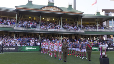 Solemn: both teams line the Sydney Cricket Ground turf before the match between Sydney Roosters and the Dragons.