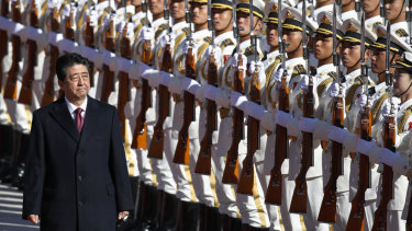 Japanese Prime Minister Shinzo Abe reviews an honor guard during a welcome ceremony at the Great Hall of the People in Beijing.