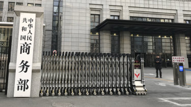 A man checks on his mobile phone near the main entrance gate of the Ministry of Commerce in Beijing.