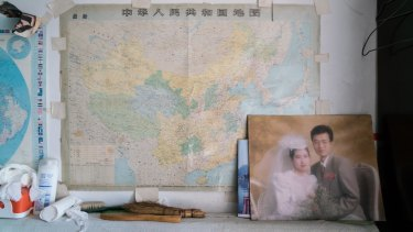 A wedding photo of Han's younger son is displayed in Han's living room/bedroom. The son's family migrated to Canada in 2003.
