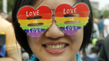 A supporter of LGBT and human rights groups wears rainbow glasses during a rally to support the bill in 2016.