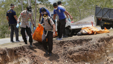 The body of a tsunami victim is taken to a mass burial site in Palu, Sulawesi, on Monday.