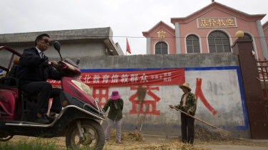 """A man rides past workers tossing hay outside a church with part of a slogan that reads """"Educate the believers with excellent Chinese traditional culture"""" near the city of Pingdingshan in central China's Henan province."""
