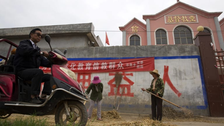 "A man rides past workers tossing hay outside a church with part of a slogan that reads ""Educate the believers with excellent Chinese traditional culture"" near the city of Pingdingshan in central China's Henan province."