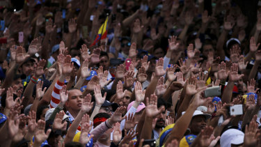 Anti-government protesters hold their hands up during the symbolic swearing-in of Juan Guaido in Caracas on Wednesday.