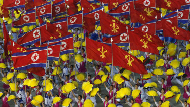 Dancers wave flags of North Korea and Korean Workers' Party as they perform during mass games. Such images are now replacing displays of military might.