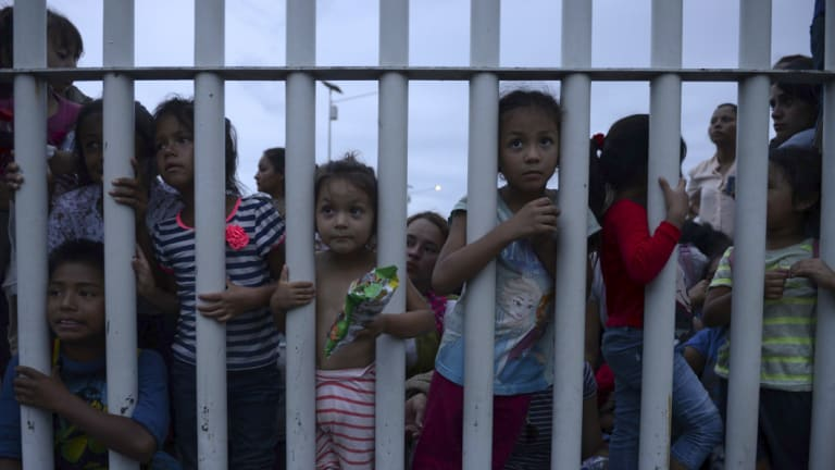Migrant children bound for the US-Mexico border wait on a bridge that stretches over the Suchiate River, connecting Guatemala and Mexico, in Tecun Uman, Guatemala, on Friday.