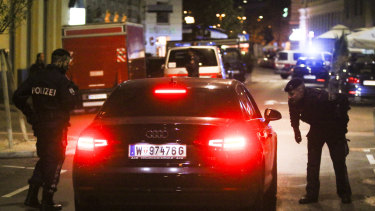 Police officers check a car at the scene after the attack in Vienna.