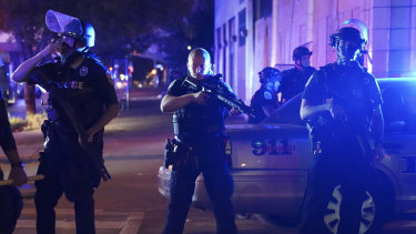 Police in Louisville stand guard after an officer was shot.