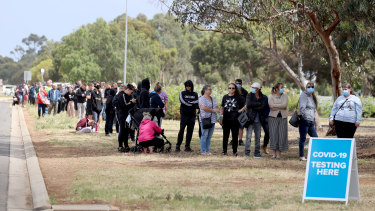 Long queues form outside a testing site at Parafield Airport in Adelaide's northern suburbs on Monday.