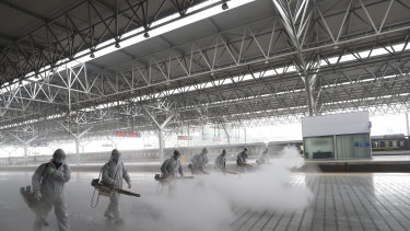 Firefighters conduct disinfection on the platform at a railway station before Wuhan's transport networks reopened in March.